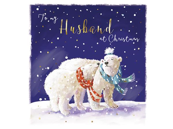 A polar bear couple together, wearing festive scarfs on a snowy night.